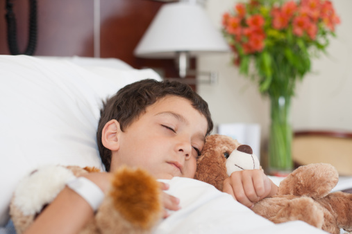 A kid sleeping at the hospital. Safe hospital sedation with general anesthesia is offered by Douglas L. Park, DDS, Pediatric Dentistry in Gresham, OR