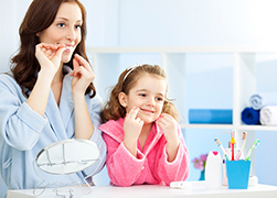 Mom flossing with daughter before visit to Douglas L. Park, DDS, Pediatric Dentistry in Gresham, OR