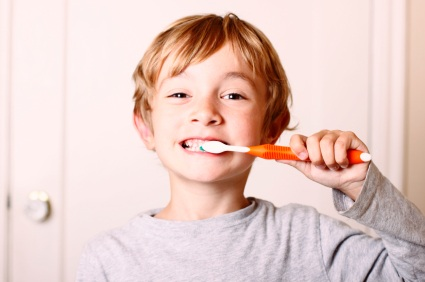 Boy standing up brushing teeth. At Douglas L. Park, DDS, Pediatric Dentistry in Gresham, OR we want to help your child succeed with dental health.