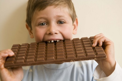 A child eating a large chocolate bar. We do our best to help prevent tooth decay at Douglas L. Park, DDS, Pediatric Dentistry in Gresham, OR