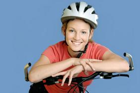 Adolescent Girl on Bicycle Wearing White Helmet riding to her appointment at Douglas L. Park, DDS, Pediatric Dentistry