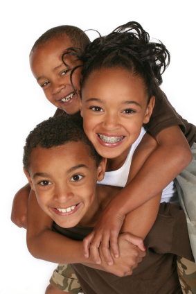 Three children hugging and smiling girl with braces from Douglas L. Park, DDS, Pediatric Dentistry